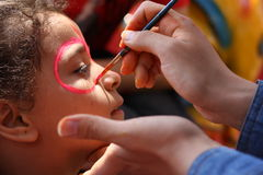 Face painting. Close-up of female hands using a brush to paint a young girl's face Royalty Free Stock Images