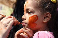 A woman painting a girls face at charity event. A woman holding a brush painting a beautiful girl face at a charity event for children, to help children, sonaa Stock Photography