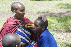Woman painting girls, Maasi Village, Ngorongoro Conservationa Ar Stock Photo