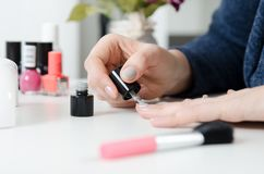 Woman painting her finger nails Royalty Free Stock Images
