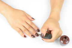 Woman painting her fingernails. With nail polish on white background Stock Photo