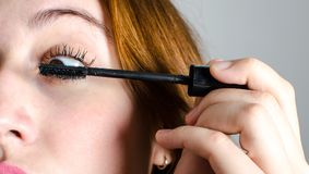 Painting her lashes. A woman painting her lashes Royalty Free Stock Photo
