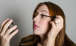 A woman painting her lashes. Stock Images