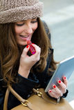 Woman painting her lips with a digital tablet. Pretty young woman painting her lips with a digital tablet on the street Stock Images