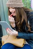 Woman painting her lips with a digital tablet. Pretty young woman painting her lips with a digital tablet on the street Royalty Free Stock Photo