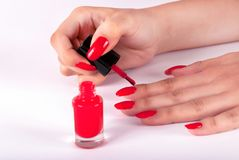 Woman painting her nails on finger in red color on white background Royalty Free Stock Photography