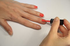Woman painting her nails. With red varnish Stock Images