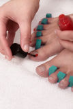 Woman painting her toenails with red varnish Stock Photo