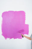 Woman painting her wall pink Royalty Free Stock Images