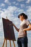 Woman painting landscape Stock Images