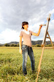 Woman painting landscape Stock Photos