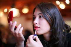 Woman painting lips Stock Images