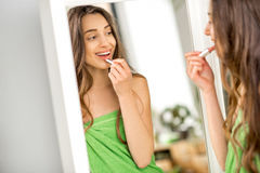 Woman painting lips in the bathroom. Beautiful woman in green towel painting lips looking at the mirror in the bathroom. Applying make-up with lipstick royalty free stock image