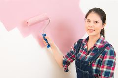 Woman painting new apartment standing. Happy beautiful young woman doing wall painting. multicultural asian chinese girl model Royalty Free Stock Image