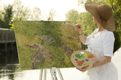 Woman painting outdoors. Woman enjoying painting next to the river Royalty Free Stock Photos