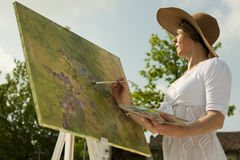 Woman painting outdoors. Woman wearing a hat enjoying painting Royalty Free Stock Photography