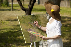 Woman painting outdoors. Woman wearing a hat enjoying painting outdoors Royalty Free Stock Images