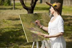 Woman painting outdoors. Woman wearing a hat enjoying painting outdoors Royalty Free Stock Image