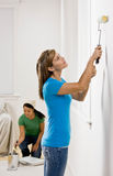 Woman painting with paint roller Stock Images