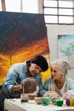 Woman painting a sculptor. In drawing class Stock Photos