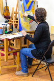 Woman painting studio easel Stock Photography