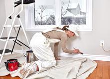 Woman painting trim. Painter woman painting room. House renovation background Royalty Free Stock Photography