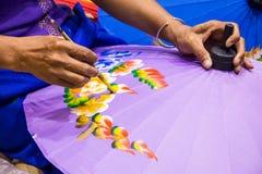 Woman painting umbrella. Royalty Free Stock Photo