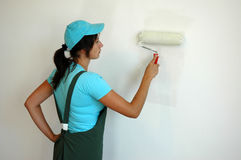 The woman is painting the wall. With roller Royalty Free Stock Image