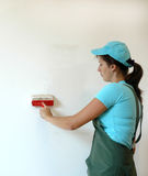 The woman is painting the wall Stock Photography