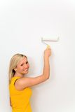 Woman painting wall. With paint roller Royalty Free Stock Photo