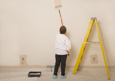 Woman Painting A Wall / Copy Space To The Left. Woman Painting A Wall With Room For Copy Space To The Left Stock Images