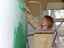 Woman painting a wall green stock images