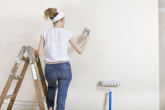 A woman painting wall on ladder Stock Image