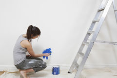 Woman Painting Wall With Paintbrush At Home. Side view of young woman painting wall with paintbrush at home Royalty Free Stock Photos