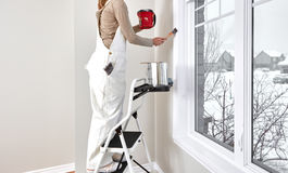 Woman painting wall Stock Image