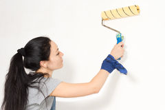 Woman painting a wall with a roller Stock Photo