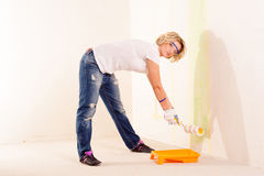 Woman painting wall with roller brush Royalty Free Stock Images
