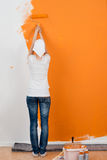 Woman Painting Wall With Roller In House. Full length rear view of young woman painting wall with roller in house Royalty Free Stock Photography