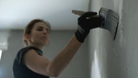 Woman is painting wall to grey colour