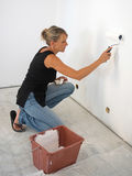 Woman painting a wall Royalty Free Stock Photos