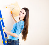 A woman is painting walls Royalty Free Stock Image