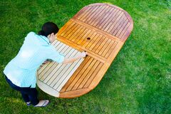 Free Woman Painting Wooden Exotic Wood Table In The Garden With A Brush Stock Image - 213087691