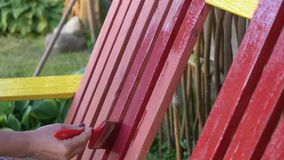 Woman paints a bench with red paint. Woman paints a bench with red paint stock video