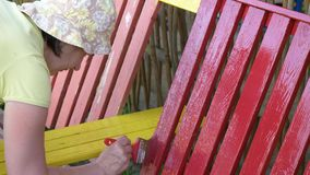 Woman paints a bench with red paint. Woman paints a bench with red paint stock video footage