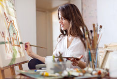 Woman paints on canvas Royalty Free Stock Photography