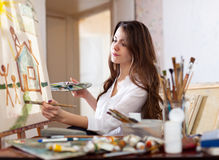 Woman paints  on canvas in workshop Stock Photography