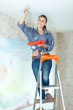 Woman paints ceiling with brush Stock Photos