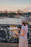 Woman paints city landmarks at evening Royalty Free Stock Photo
