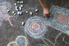 Woman paints with colored chalk on asphalt - Stock Image Royalty Free Stock Images