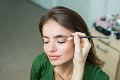 Woman paints the eyebrows royalty free stock photo
